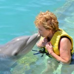 Grandma kissing a dolphin