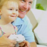 stock-footage-young-caucasian-father-pre-school-daughter-playing-electronic-games-console-home-sofa-close-up-shot